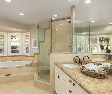 Luxury bathroom interior in marble with glass shower and round d